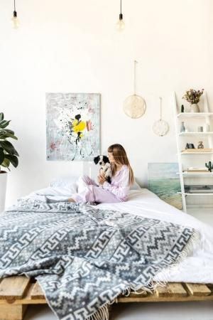 young woman in pajamas hugging puppy while sitting on bed in morning at home
