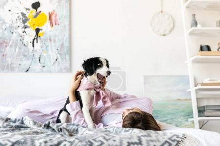young woman in pajamas lying on bed together with black and white puppy