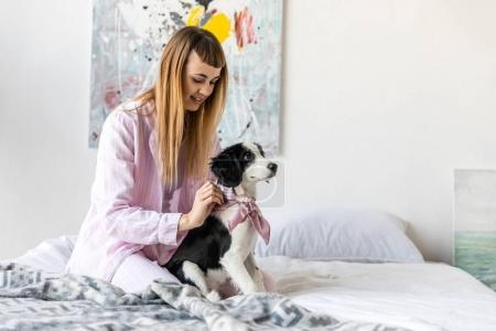 smiling woman in pajamas and cute little puppy resting on bed in morning at home