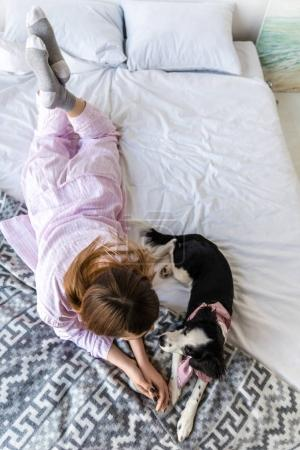 overhead view of woman in pajamas lying on bed together with cute puppy