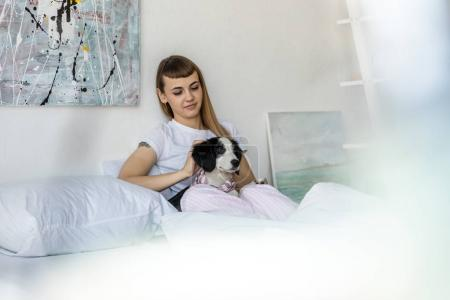 Photo for Portrait of young woman with little puppy resting in bed in morning at home - Royalty Free Image
