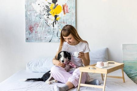 woman drinking coffee while resting in bed together with puppy
