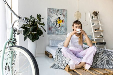 young woman drinking coffee while resting on bed in morning at home