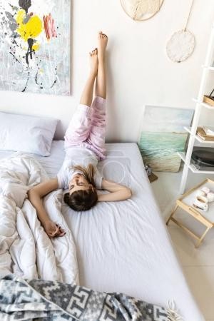 Photo for Young woman in pajamas resting on bed in morning at home - Royalty Free Image