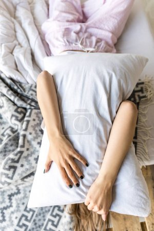obscured view of woman hugging pillow while lying in bed