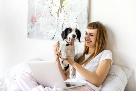Foto de Retrato de mujer feliz jugando con el cachorro en la mañana en casa - Imagen libre de derechos