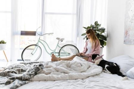 Photo pour Jeune femme utilisant un ordinateur portable le matin à la maison - image libre de droit