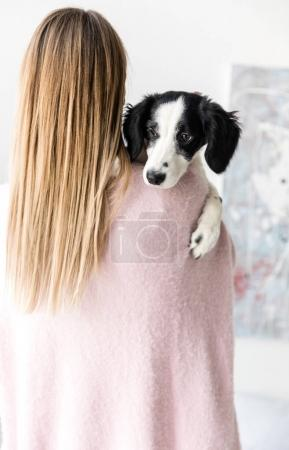 rear view of woman holding cute black and white puppy