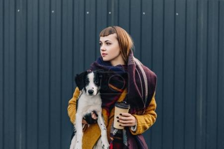 portrait of pensive woman holding puppy and coffee to go in hands while standing on street