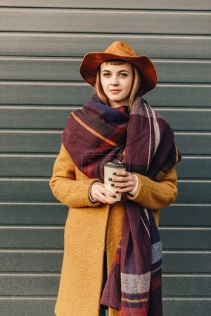 Photo for Portrait of attractive woman in autumn jacket and hat with coffee to go in hands - Royalty Free Image