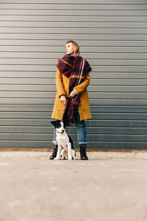 fashionable woman with puppy on dog lead standing on street