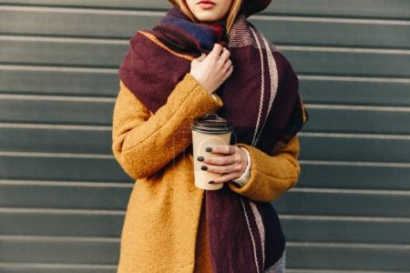 Photo for Partial view of woman in autumn jacket and hat with coffee to go in hand - Royalty Free Image
