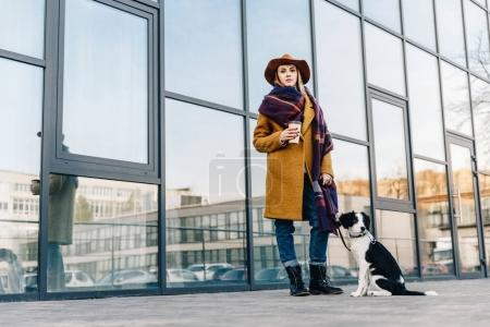 stylish woman in hat and jacket with puppy on dog lead posing on street