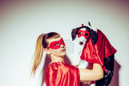 side view of young woman and puppy in superhero costumes