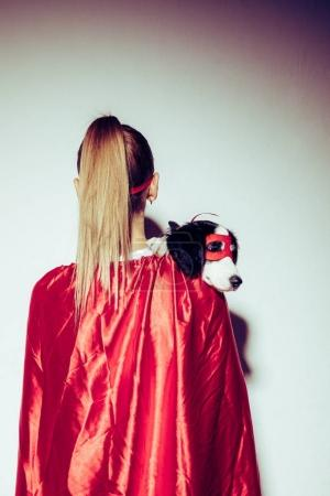 back view of woman in red cape holding little puppy in superhero mask