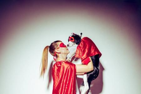 side view of young woman and little puppy in red masks and capes