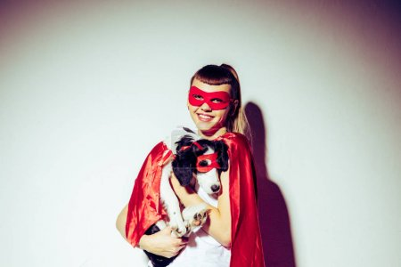 portrait of smiling woman holding puppy in superhero costume