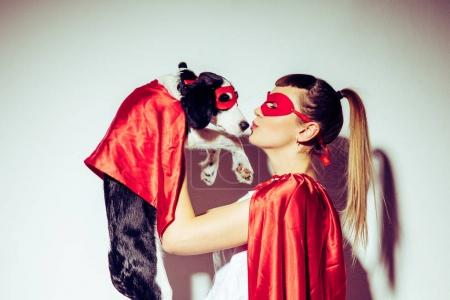 side view of woman kissing puppy in superhero costume