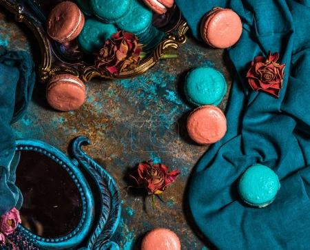 Photo for Composition with blue and pink macarons, dried roses and mirror on a rustic surface. - Royalty Free Image