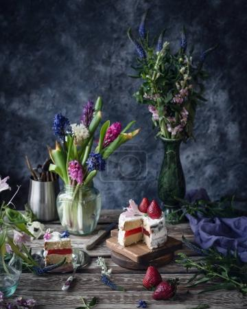 Cake with strawberry and flower on wooden table