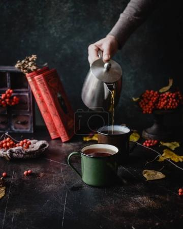 Photo for Female hand pouring black tea in enamel mugs, autumn leaves and red berries on dark shabby background - Royalty Free Image