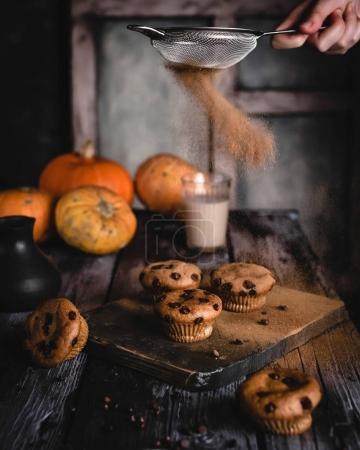 Photo pour Poudre de cannelle à la main féminine sur muffins avec chocolat sur planche de bois, verre de lait et citrouilles sur fond bois foncé - image libre de droit
