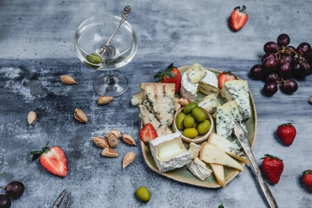 Photo for Plate with set of cheese and strawberries and olives with martini glass on grunge background - Royalty Free Image
