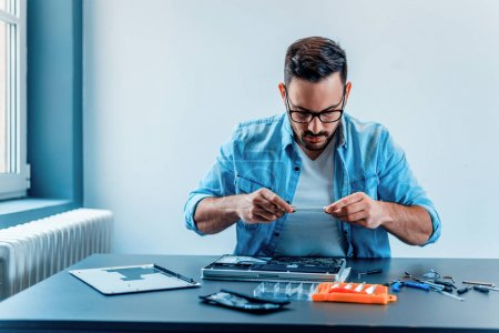 Focused technician photographing disassembled laptop