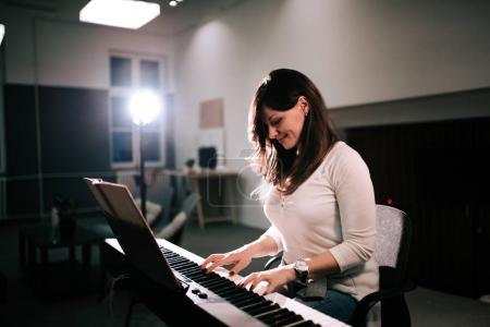 Smiling woman pianist playing synthesizer from sheet music