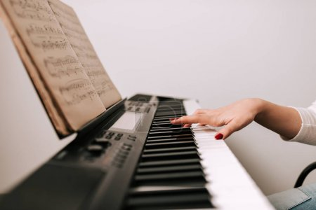 Female hand playing piano from classical sheet music