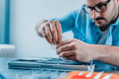 Close-up of computer technician fixing laptop hardware.