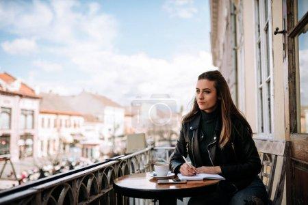 Photo pour Belle fille étudiant en plein air dans un café . - image libre de droit