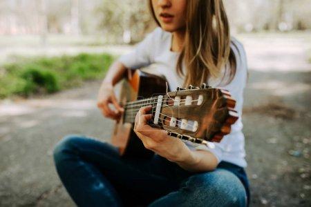 Photo pour Jeune femme jouant de la guitare acoustique dans le parc de la ville - image libre de droit