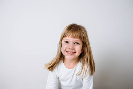 Portrait of smiling blonde girl against white background