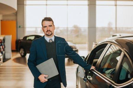 Photo pour Vendeur de voitures debout à côté de la voiture au showroom . - image libre de droit