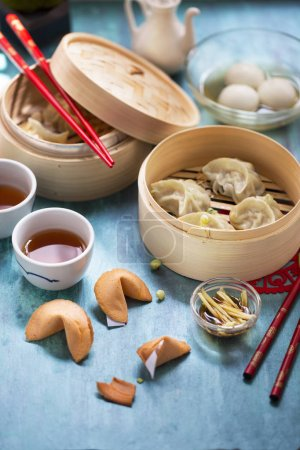 Photo for Chinese new year food and drinks, steamed dumplings in bamboo steamer, fortune cookies on wooden blue tabletop - Royalty Free Image