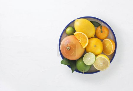 Photo for Fresh citrus fruits in bowl on white background - Royalty Free Image