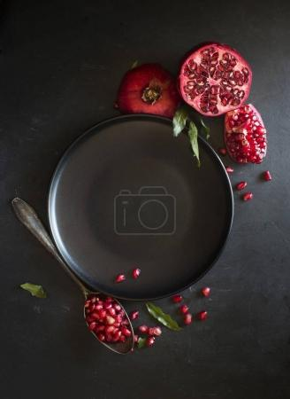 Photo for Fresh ripe sliced pomegranate on black surface with black plate and spoon - Royalty Free Image