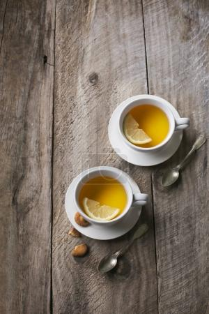 Two cups of lemon herbal tea on rustic wooden table top. Overhead view.