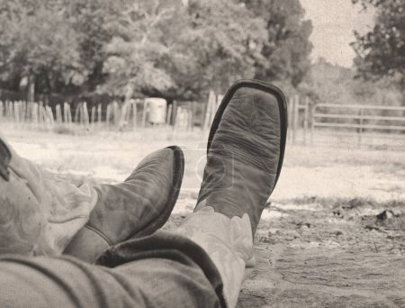 Photo for Black and white photo of cowboy boots on legs, shows ranch western wear - Royalty Free Image
