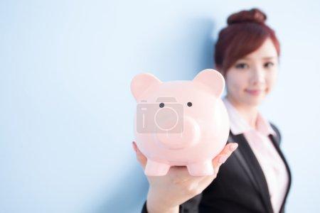 Photo pour Femme d'affaires prendre rose tirelire et sourire à vous avec fond bleu - image libre de droit