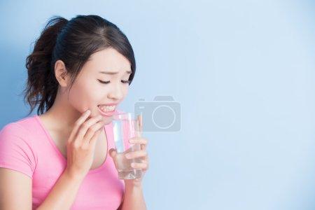 Photo pour Femme boire de l'eau avec des dents sensibles isolées sur fond bleu - image libre de droit