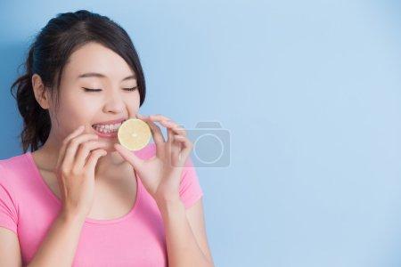 Photo pour Femme mangeant du citron solitaire sur fond bleu - image libre de droit