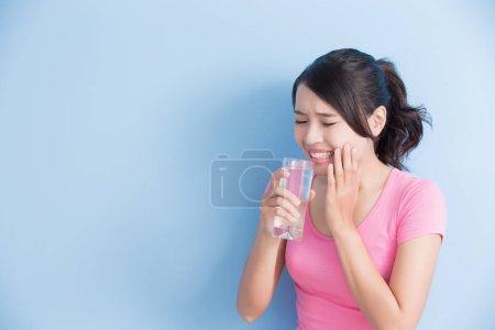 Photo pour Femme aux dents sensibles boire de l'eau isolée sur fond bleu - image libre de droit