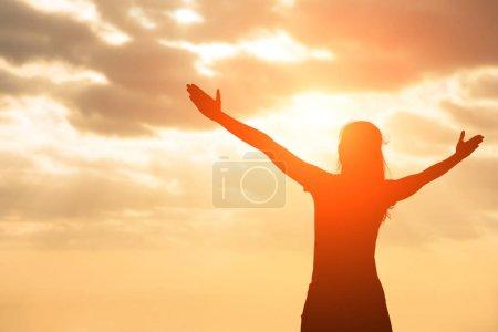 Photo pour Silhouette de femme prier avec la lumière du soleil - image libre de droit