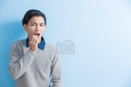 Photo pour Homme sentir mal de dents avec fond bleu, asiatique - image libre de droit