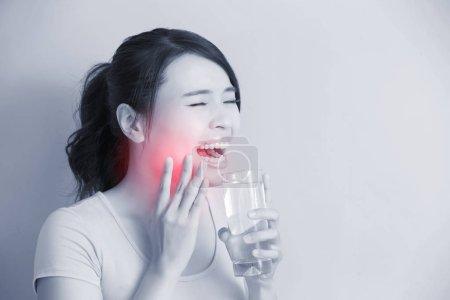 Photo pour Femme boire de l'eau avec des dents sensibles, asiatique - image libre de droit