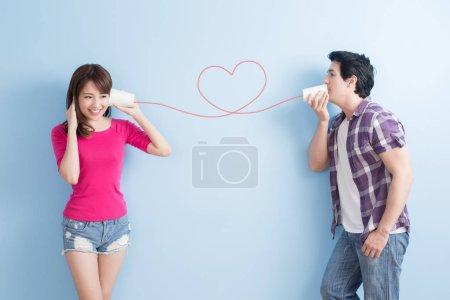Photo pour Jeune couple avec des canettes parler isolé sur fond bleu - image libre de droit