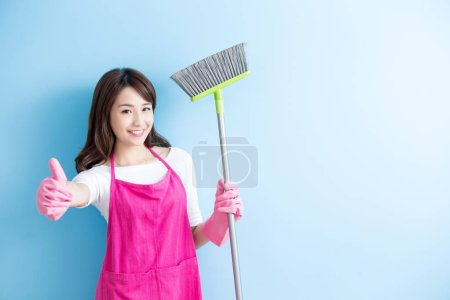 Housewife with  broom showing  thumb up isolated o...