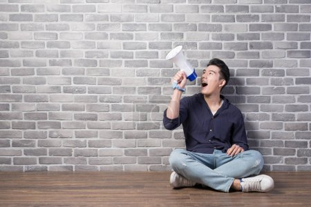 Photo for Handsome man sitting  with megaphone with brick wall background,  asian - Royalty Free Image